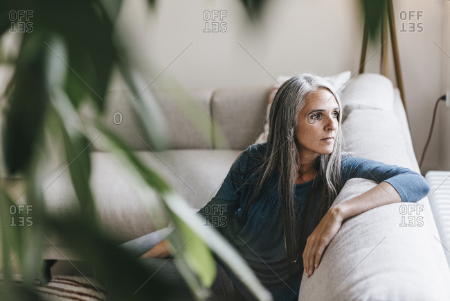 Pensive woman sitting on the couch looking through window