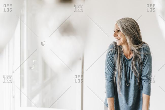 Happy woman looking through window
