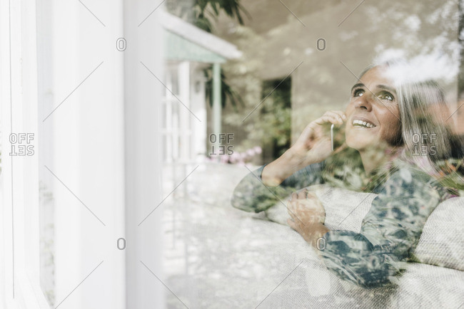 Smiling woman on the phone sitting behind windowpane on the couch looking up