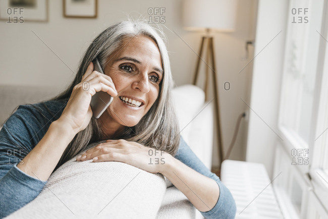 Smiling woman sitting on the couch telephoning with cell phone