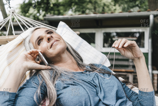 Smiling woman on the phone lying in hammock in the garden
