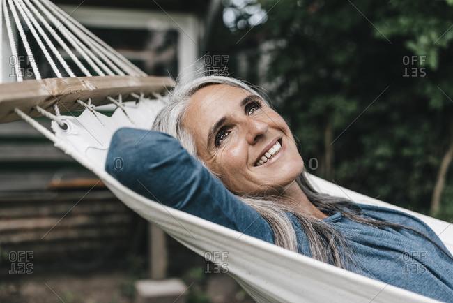 Portrait of smiling woman lying in hammock in the garden