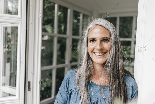Portrait of happy woman with long grey hair leaning against door case of her winter garden