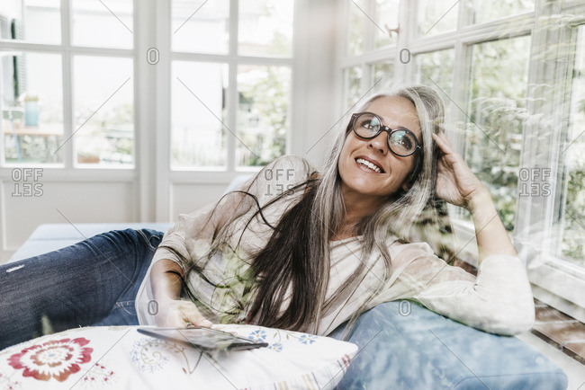 Portrait of smiling woman with e-book lying on lounge in her winter garden