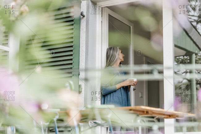 Woman leaning at terrace door with cup of coffee
