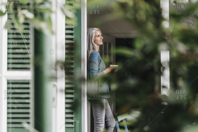 Smiling woman leaning at door frame with cup of coffee at home