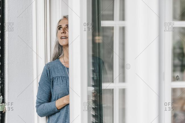 Woman standing at open terrace door looking up