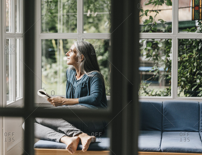 Relaxed woman sitting with book on lounge in winter garden looking through window