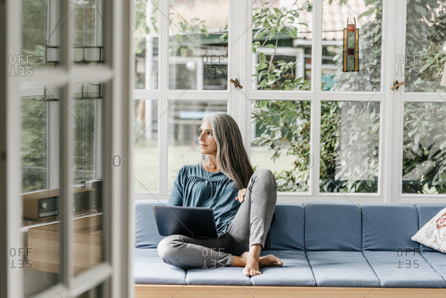 Woman sitting on lounge in winter garden with laptop