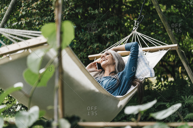 Woman on the phone relaxing in hammock in the garden