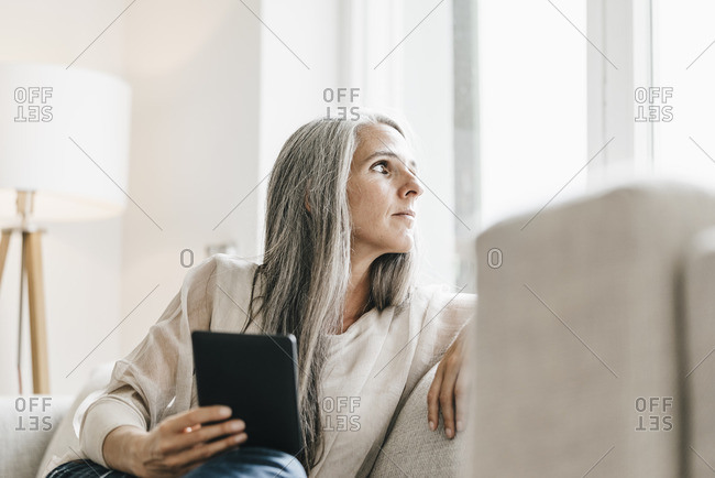 Woman with e-book sitting on the couch looking through window