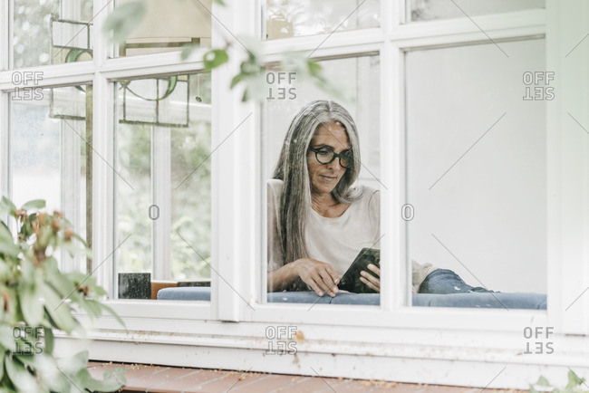 Woman sitting in winter garden reading e-book