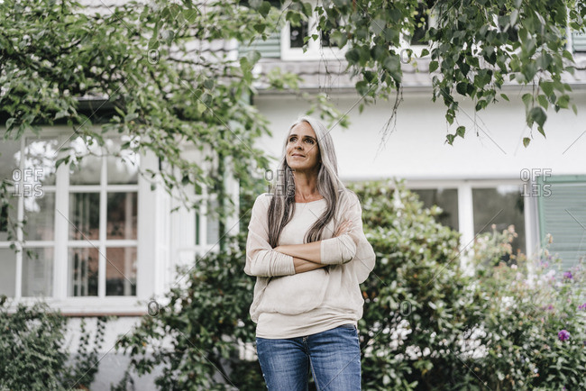 Smiling woman with long grey hair standing in the garden
