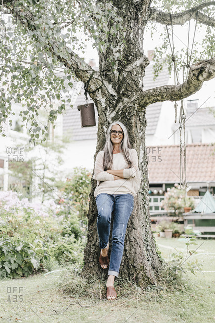 Smiling woman with long grey hair leaning against tree in the garden