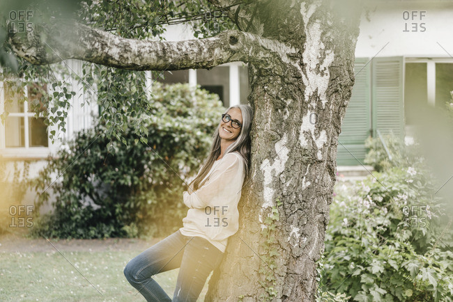 Smiling woman leaning against tree in the garden