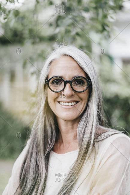 Portrait of smiling woman with long grey hair wearing spectacles