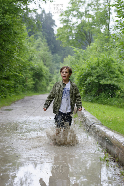 Germany, East Allgaeu, near Fuessen, Alluvial Forest, nature trail, wood experience center Ziegelwies, boy hopping in puddle