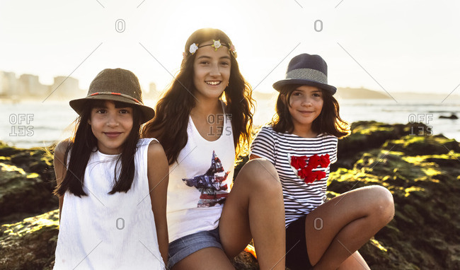 Three smiling girls on the beach at sunset