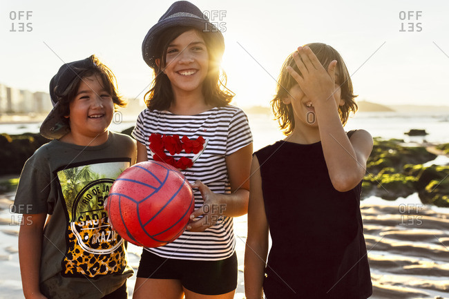 Three happy kids with ball on the beach at sunset