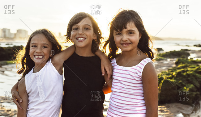 Portrait of three happy kids on the beach at sunset