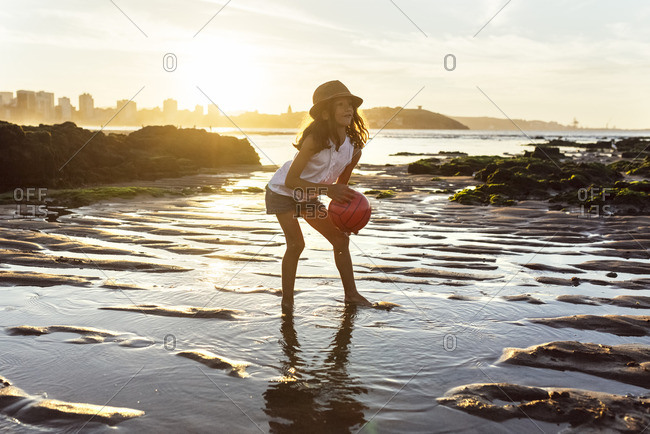 Girl playing with a ball on the beach at sunset