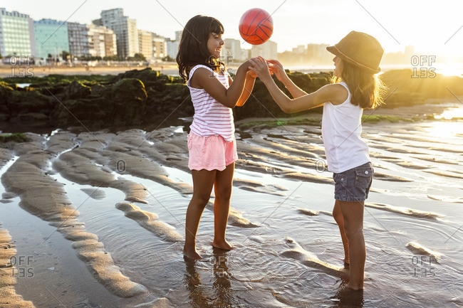 Two girls playing with a ball on the beach at sunset