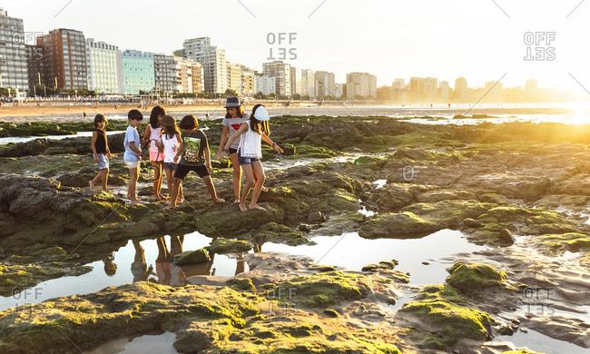 Kids walking on rocky beach at sunset