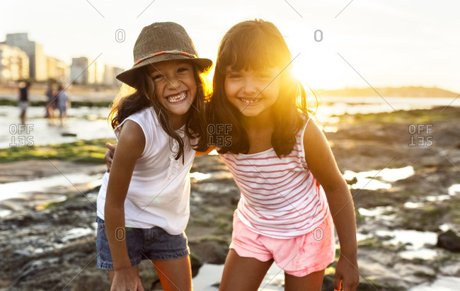 Portrait of two smiling girls on the beach at sunset