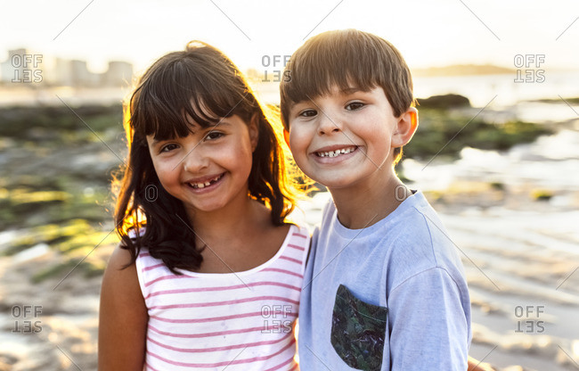 Portrait of two smiling kids on the beach at sunset