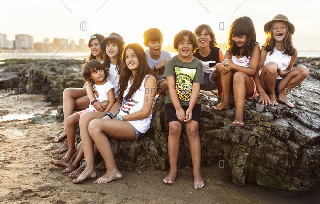 Group of kids sitting on rock on the beach at sunset