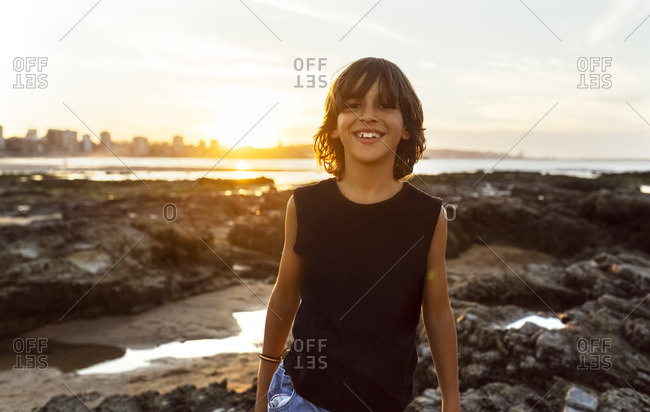 Smiling boy on the beach at sunset