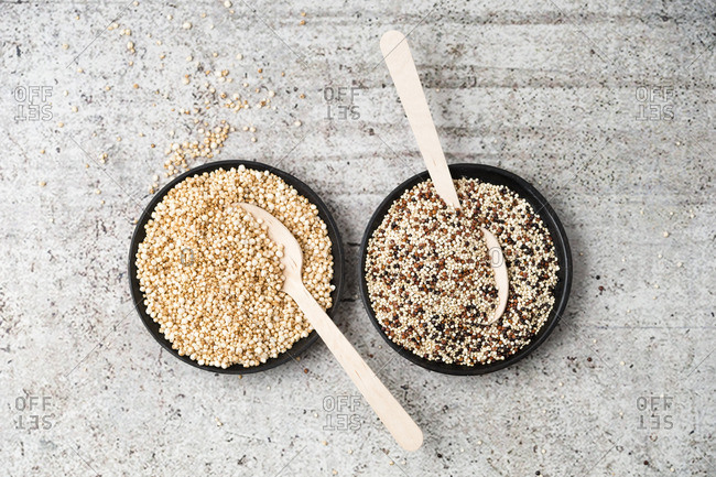 Wholemeal quinoa and popped quinoa in bowls, wooden spoons