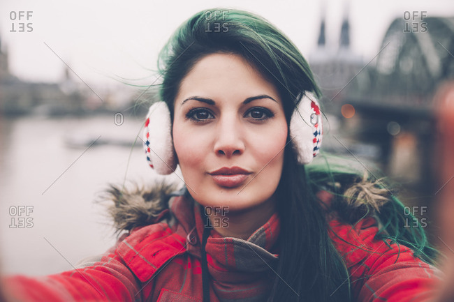 Germany, Cologne, portrait of woman with ear muffs taking selfie