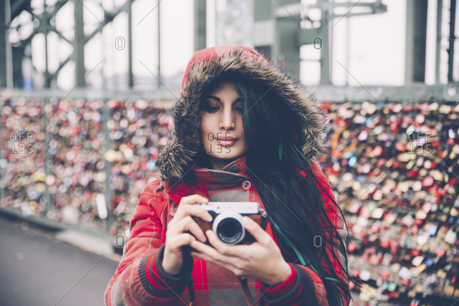 Germany, Cologne, woman with camera at Hohenzollern Bridge