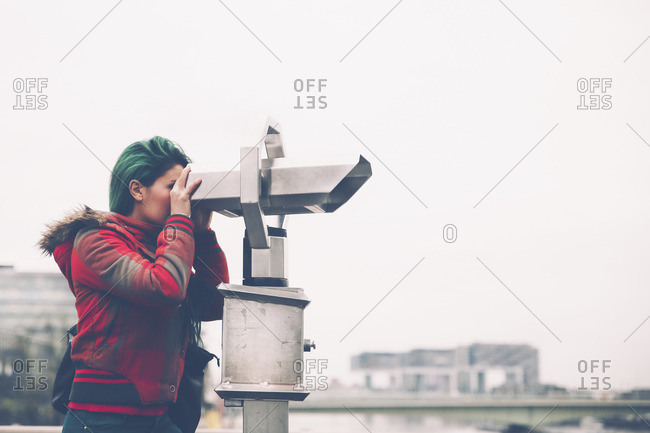 Germany, Cologne, woman looking through coin operated binoculars