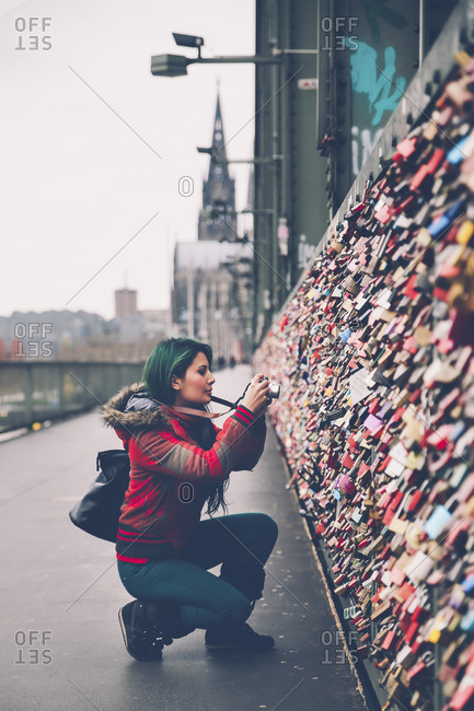 Germany, Cologne, woman taking picture of love locks at Hohenzollern Bridge