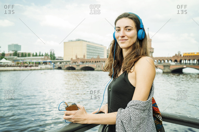 Germany, Berlin, portrait of relaxed woman listening music with headphones