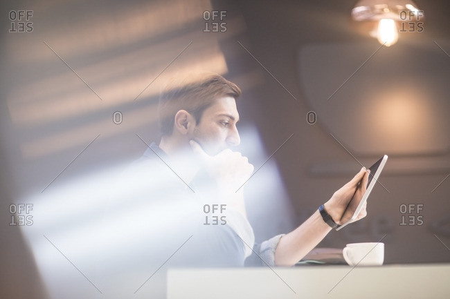 Man with digital tablet at office desk thinking