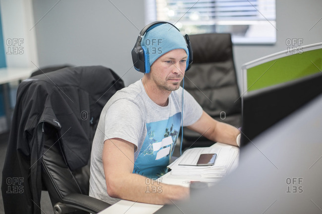 Young man wearing headphones working on computer in office
