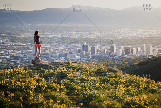 Female Trail Runner Exploring Salt Lake City From A Field Of Wildflowers