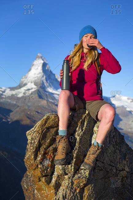Female Hiker Drinking Tea From A Thermos Bottle In The Swiss Alps Above Zermatt