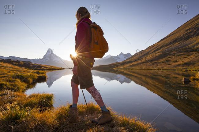 Female Hiker Is Standing At Stellisee Lake Near Matterhorn During Sunset