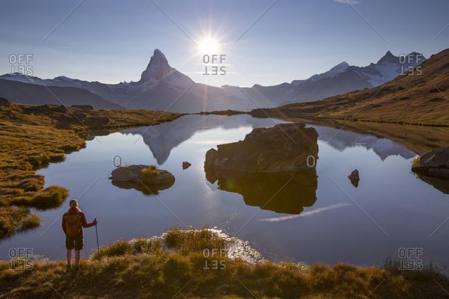 Female Hiker Standing At The Stellisee Lake Near Matterhorn During Sunset