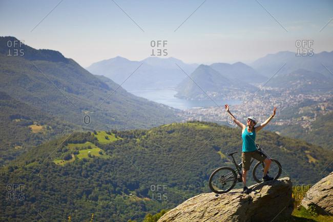 Female Mountain Biker Waving Hand On Top Of A Rock