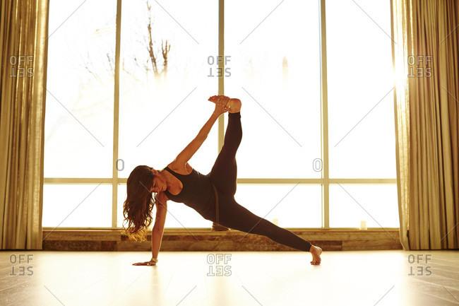 Woman Doing Exercise In Yoga Studio