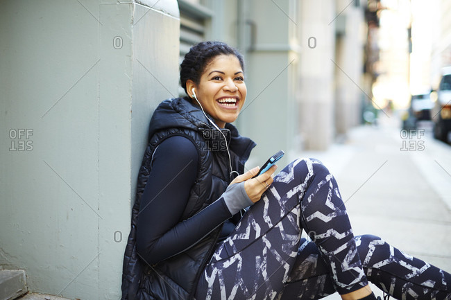 Smiling Woman With Headphones And A Smartphone In Boston