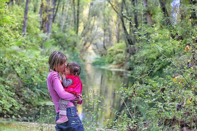 Mother Kissing Daughter On Chick In Forest Of Poplars And Pines