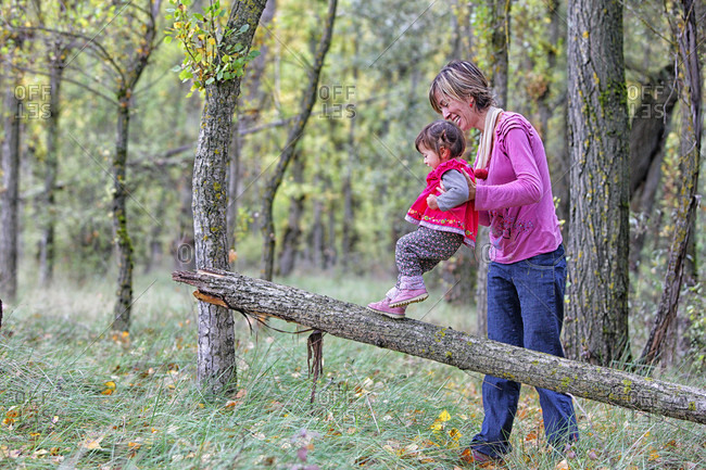 Mother Guiding Daughter To Walk On Log In Forest Of Poplars And Pines