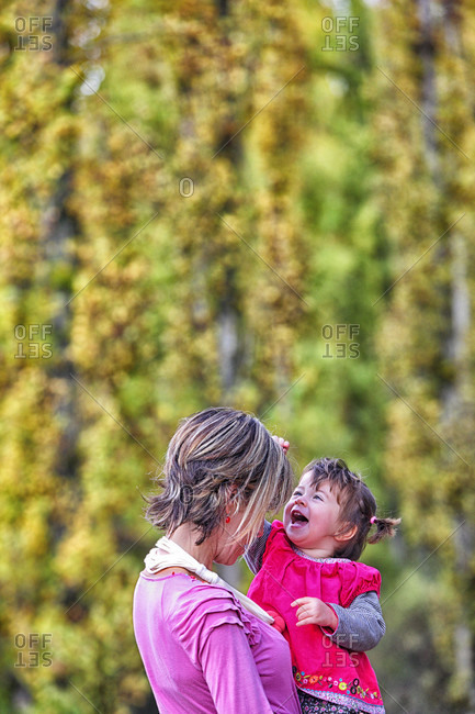 Smiling Girl Playing With Her Mother In Forest Of Poplars And Pines