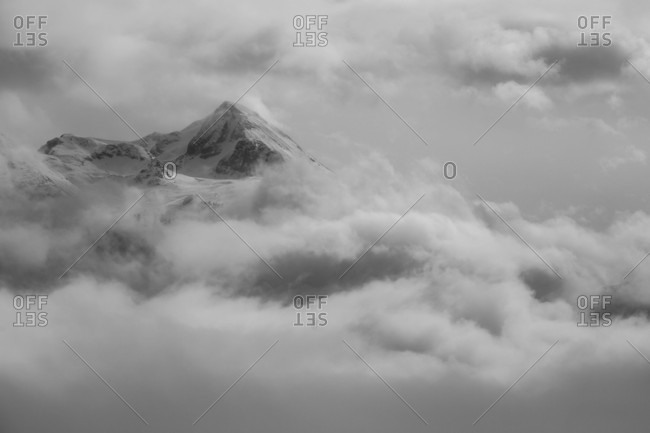 Snowcovered Rocky Peak Rising Through Heavy Clouds In British Columbia